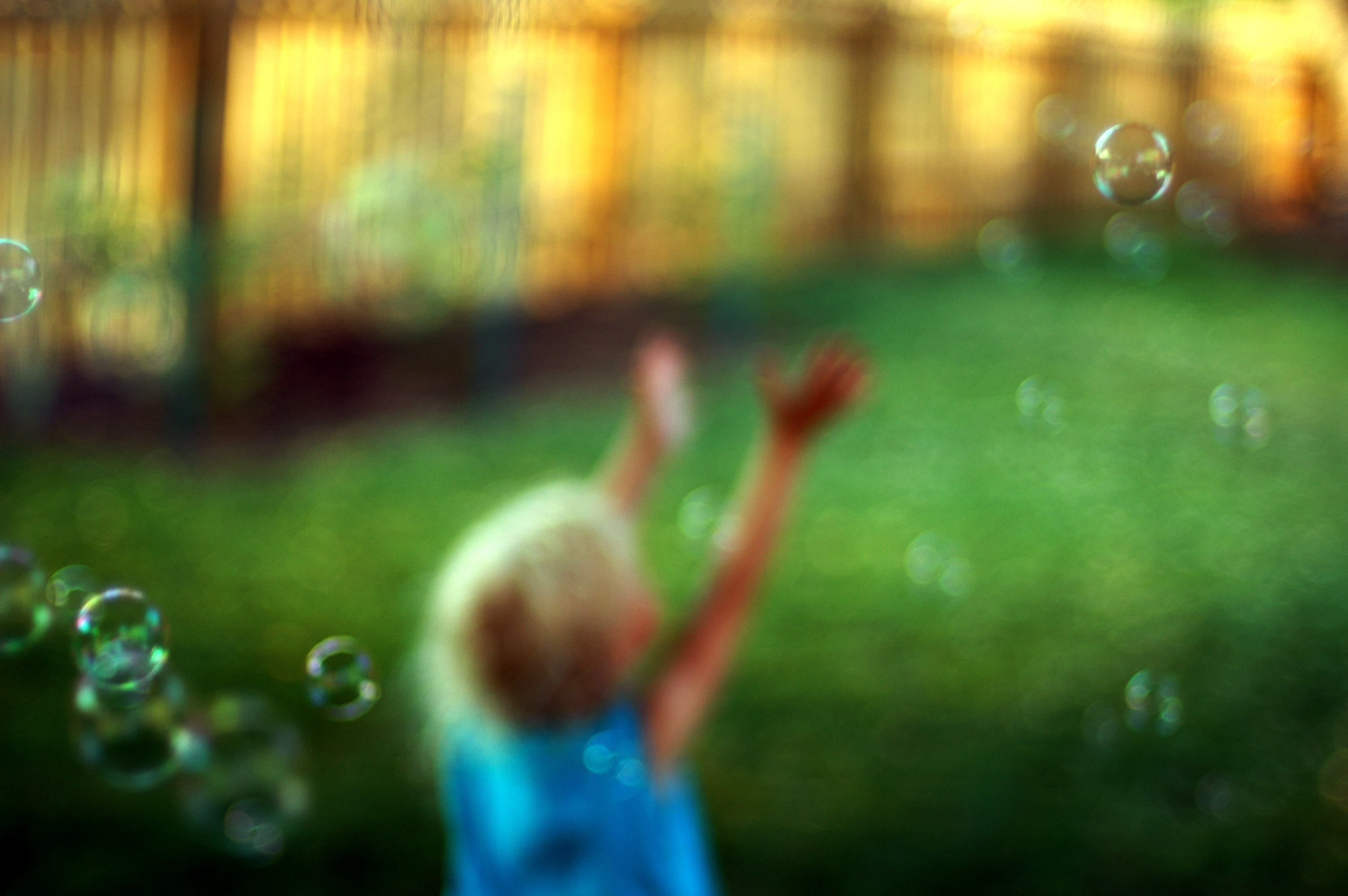 blurry image of a child catching bubbles