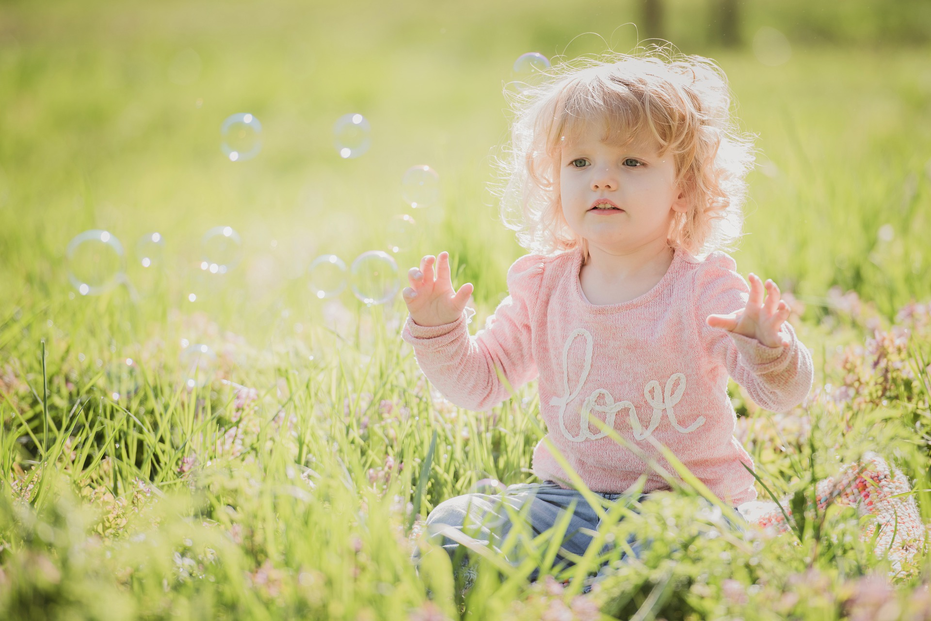 child sat in a meadow