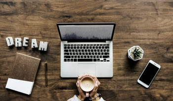 blogging as a living, laptop, mug, plant, phone and book on a desk